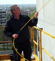 Om Jydsk Tag & Facade - Chefen Ronald igang med at rense og imprægnere facade.